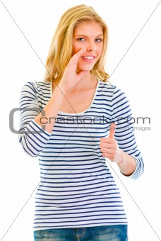Smiling beautiful teen girl reporting good news and  showing thumbs up gesture
