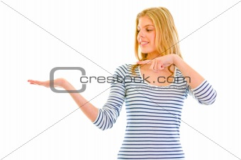Smiling beautiful teen girl pointing finger on empty hand