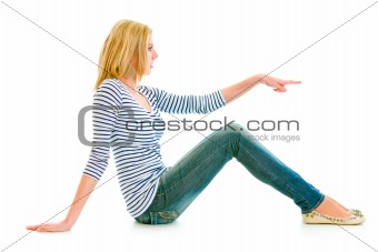 Beautiful teen girl sitting on floor and pointing finger at copy-space