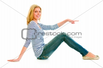 Smiling beautiful teen girl sitting on floor and pointing finger at something