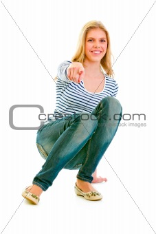 Smiling beautiful teen girl squatting and pointing finger at you