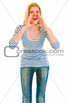Funny beautiful teen girl shouting through megaphone shaped hands
