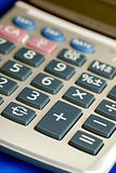 Close up view of a calculator isolated on blue