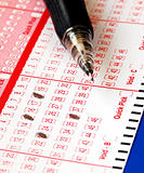 Filing the lottery ticket with a pencil isolated on blue