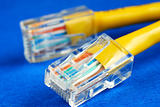 Close-up view of the yellow Ethernet (RJ45) network cable isolated on blue