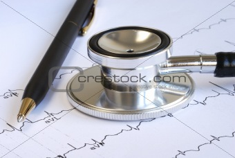 A stethoscope and a pen on the top of the EKG graph