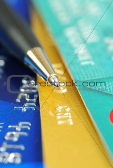 A pen on the top of several credit cards