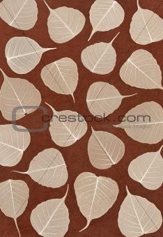 Skeletal leaves over brown handmade paper - background