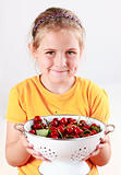 Child holding a bowl of fresh cherries