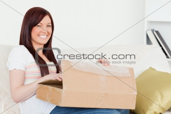Beautiful red-haired woman opening a carboard box while sitting