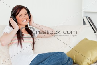 Attractive red-haired woman listening to music with headphones w