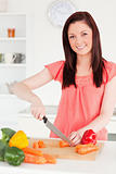 Beautiful red-haired woman cutting some carrots in the kitchen