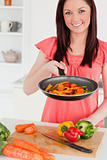 Good looking red-haired woman cooking vegetables in the kitchen