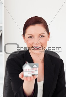 Attractive red-haired woman in suit holding a miniature house