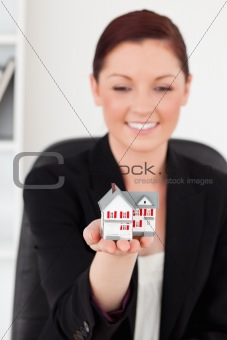 Beautiful red-haired woman in suit holding a miniature house