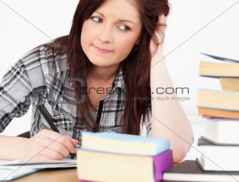 Attractive red-haired girl studying for an examination