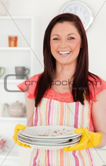Beautiful red-haired woman holding some dirty plates in the kitc