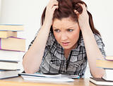 Attractive red-haired female being upset while studying for an e