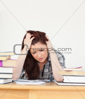 Attractive red-haired female being depressed while studying for