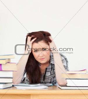 Beautiful red-haired female being depressed while studying for a