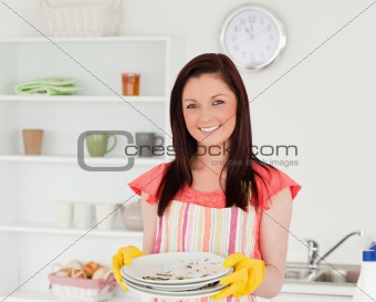 Attractive red-haired woman holding some dirty plates in the kit