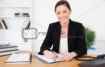 Beautiful red-haired female in suit writing on a notepad and pos