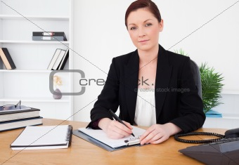 Attractive red-haired female in suit writing on a notepad and po