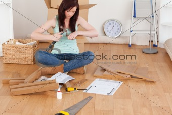 Beautiful red-haired girl using a hammer for diy at home