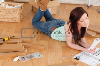 Beautiful red-haired girl reading a manual before do-it-yourself