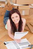 Good looking red-haired girl posing while reading a manual befor