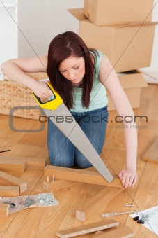 Beautiful red-haired woman using a saw
