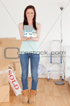 Beautiful red-haired woman holding a miniature house standing on