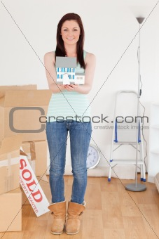 Attractive red-haired woman holding a miniature house standing o