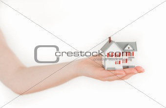 Arm holding a miniature house on a white background
