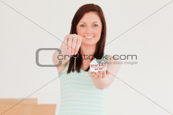 Attractive red-haired female holding a key and a miniature house