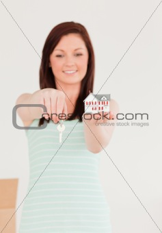 Beautiful red-haired female holding a key and a miniature house