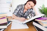 Beautiful red-haired female studying at her desk