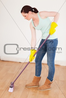 Beautiful red-haired woman sweeping the floor at home
