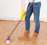 Attractive red-haired woman sweeping the floor at home