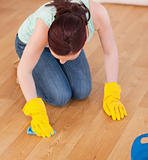 Attractive red-haired woman cleaning the floor while kneeling
