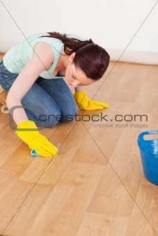 Pretty red-haired woman cleaning the floor while kneeling