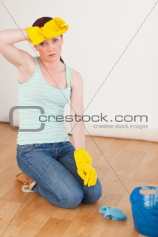 Good looking red-haired woman having a break while cleaning the