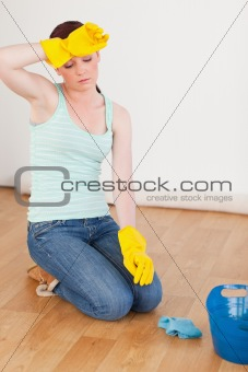Attractive red-haired woman having a break while cleaning the fl