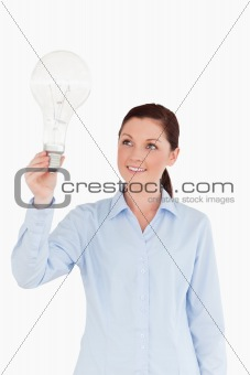 Attractive red-haired female holding a light bulb while standing