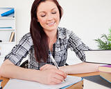 Lovely red-haired female studying at her desk