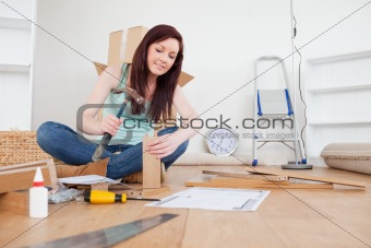 Attractive red-haired female nailing a plank at home