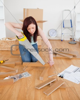 Attractive red-haired female using a saw for diy at home