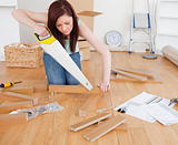 Good looking red-haired female using a saw for diy at home