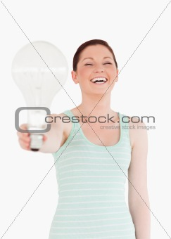 Beautiful red-haired female holding a bulb while standing