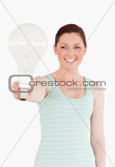 Beautiful red-haired female holding a light bulb while standing
